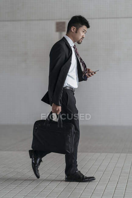 Young businessman with cell phone walking in the city — Stock Photo