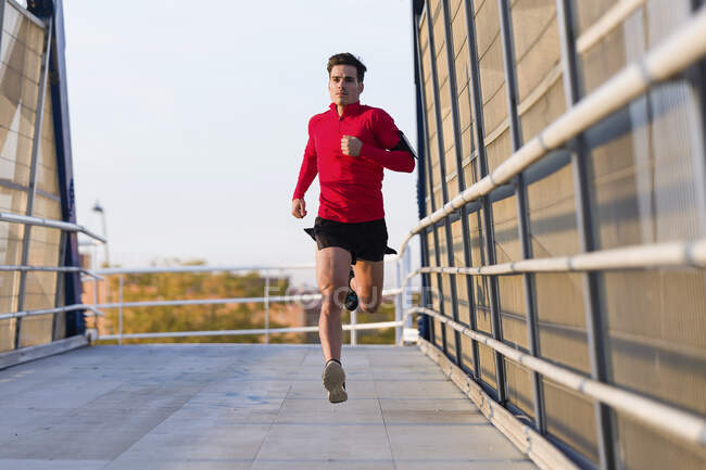 Jogger with smartphone in arm pocket running on a bridge — Stock Photo