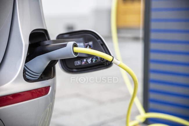 Voiture électrique gettig chargé à une station de recharge — Photo de stock