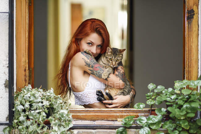 Portrait of red-haired tattooed woman with her cat at the window — Stock Photo