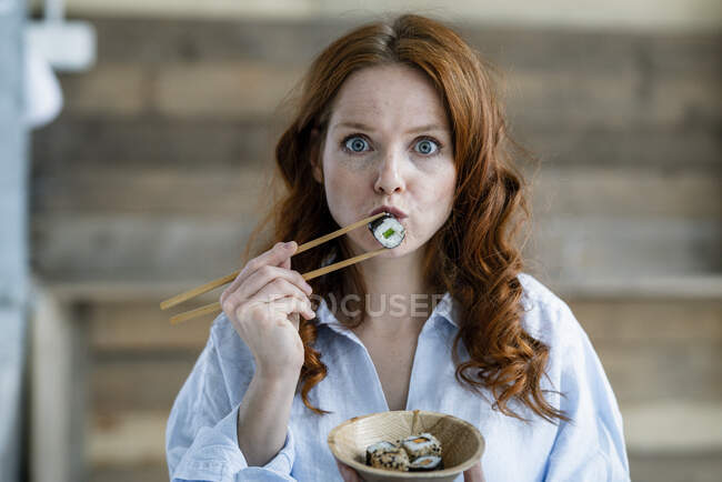 Portrait of redheaded woman eating sushi — Stock Photo