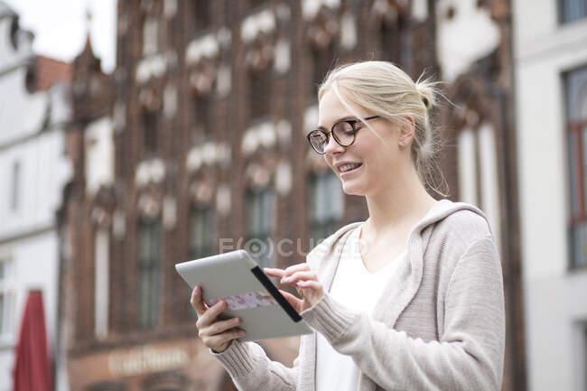 Retrato de una joven usando tableta en la ciudad - foto de stock