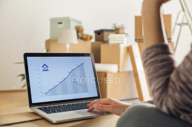 Woman using laptop with rising line graph on the screen in a new home — Stock Photo