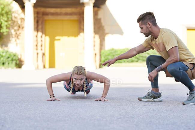 Тренер по фитнесу практикуется с молодой женщиной на открытом воздухе в городе — стоковое фото