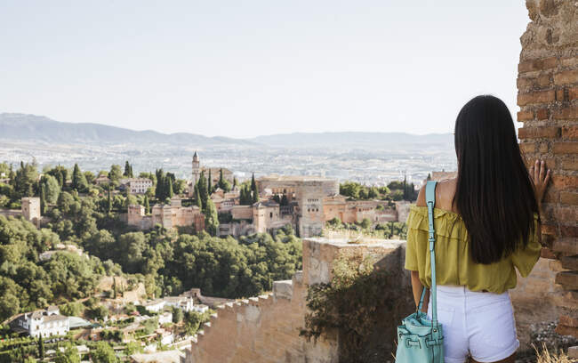 Rear view of young woman looking at the Alhambra, Granada, Spain — Stock Photo
