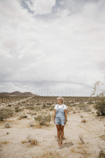 Young woman jumping mid-air in desert landscape, Joshua Tree National Park, California, USA — Stock Photo