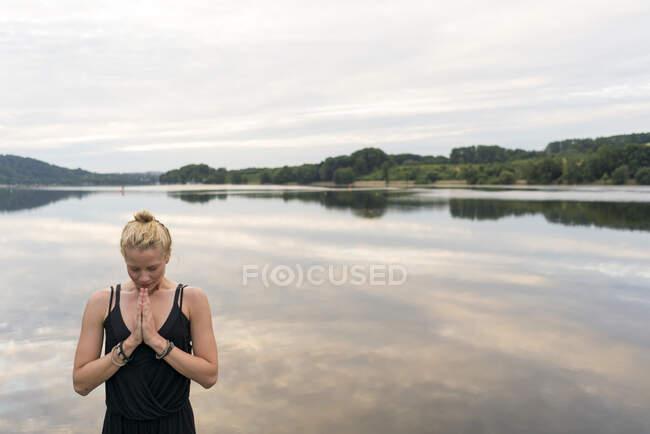 Giovane donna con le mani giunte in un lago — Foto stock