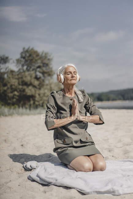 Старшая женщина медитирует в наушниках на пляже — стоковое фото