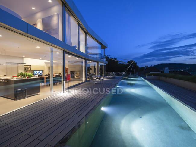 Svizzera, villa moderna illuminata al tramonto con terrazza e piscina in primo piano — Foto stock