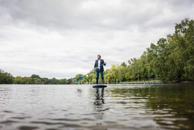 Empresario de pie remando en un lago - foto de stock