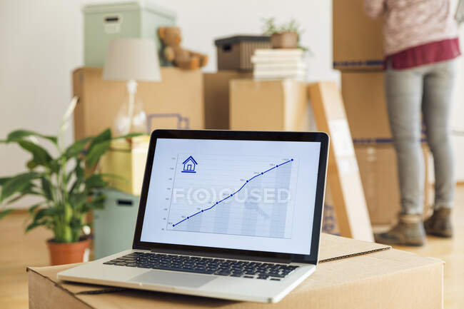 Rising line graph on laptop screen in front of cardboard boxes in a new home — Stock Photo