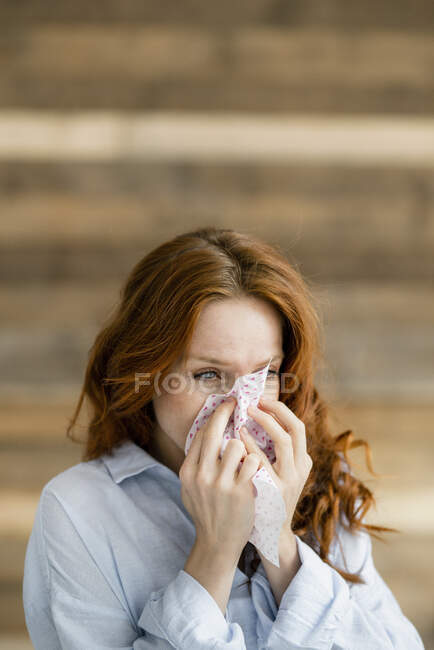 Redheaded woman blowing nose — Stock Photo