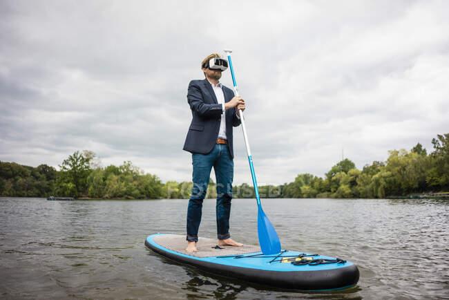 Empresario con gafas VR a bordo de SUP en un lago - foto de stock
