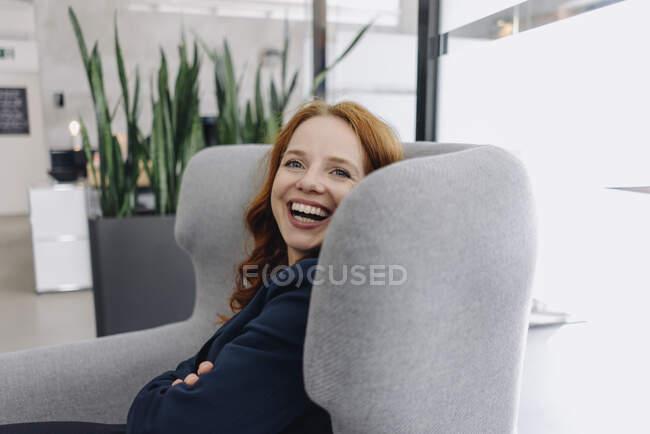 Feliz mulher de negócios ruiva sentada em poltrona — Fotografia de Stock