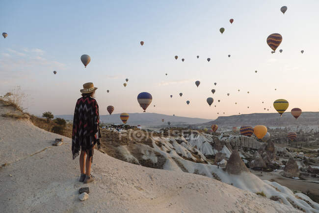 Young woman and hot air balloons in the evening, Goreme, Cappadocia, Turkey — Stock Photo