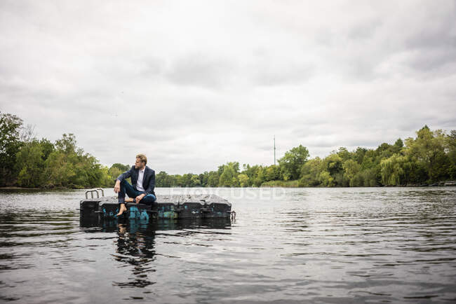 Empresario sentado en un flotador en un lago - foto de stock