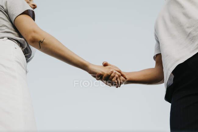 Молода пара тримається за руки — стокове фото
