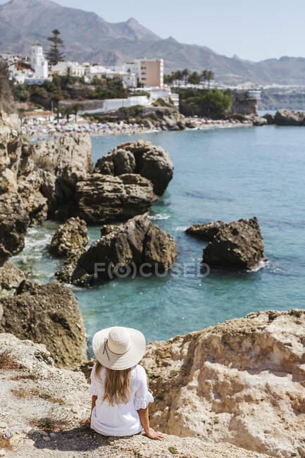 Vista trasera de la mujer vestida de blanco y sombrero de paja sentado en las rocas mirando al mar, Nerja, España - foto de stock
