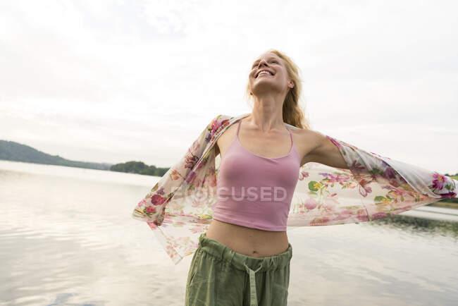 Happy young woman at a lake — Stock Photo