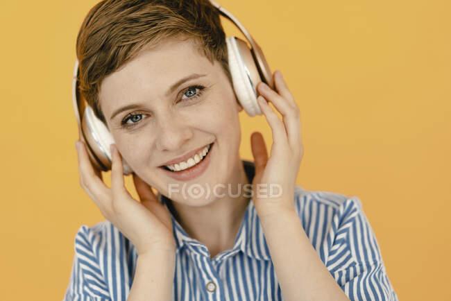 Портрет счастливой женщины, слушающей музыку на оранжевом фоне — стоковое фото