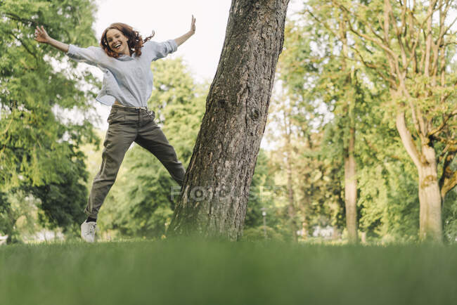 Portrait of happy redheaded woman in a park — Stock Photo