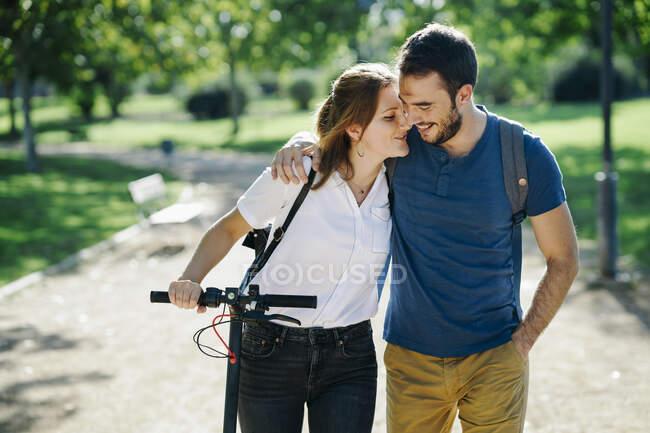 Щаслива пара з електричним скутером у міському парку. — стокове фото
