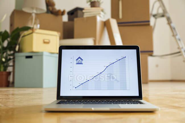 Gráfico en línea ascendente en la pantalla del ordenador portátil delante de cajas de cartón en una habitación vacía en un nuevo hogar - foto de stock