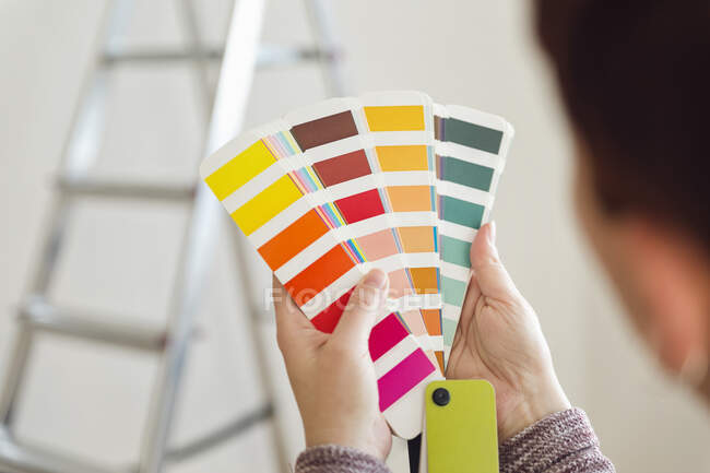 Woman holding colour sample in an empty room with a ladder — Stock Photo