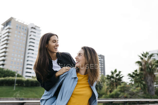 Laughing woman carrying her best friend piggyback in a park — Stock Photo