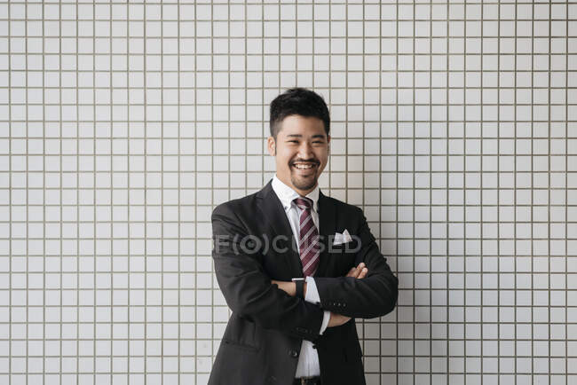 Portrait of happy young businessman at tiled wall — Stock Photo