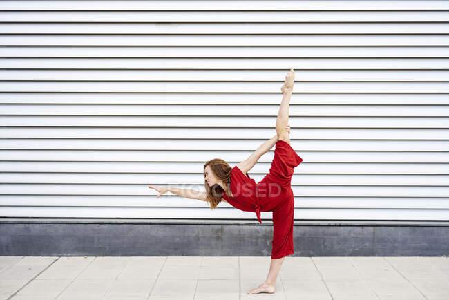 Спортивная молодая женщина занимается акробатикой на открытом воздухе — стоковое фото