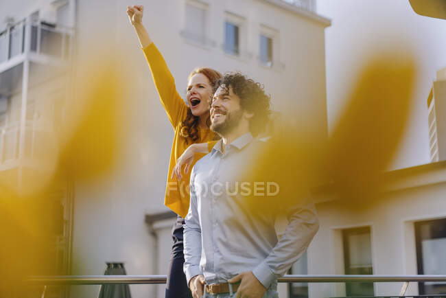 Woman with colleague on roof terrace clenching fist — Stock Photo