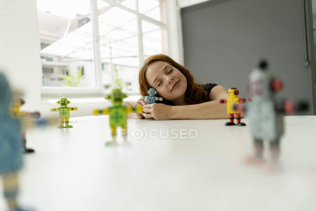 Portrait of redheaded businesswoman in a loft with miniature robots on desk — Stock Photo