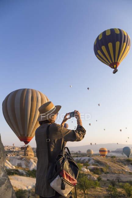 Mujer joven y globos de aire caliente, Goreme, Capadocia, Turquía - foto de stock