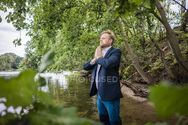 Empresario de pie en un lago meditando - foto de stock