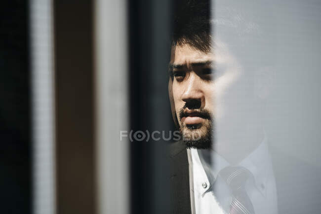 Portrait of young businessman reflected in the window — Stock Photo