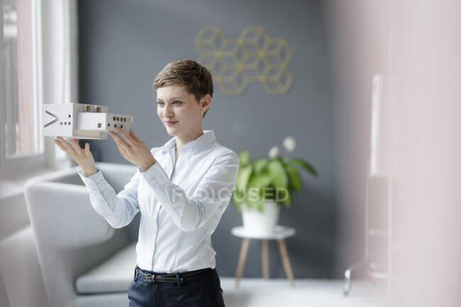 Fiduciosa donna d'affari che detiene un modello architettonico in ufficio — Foto stock