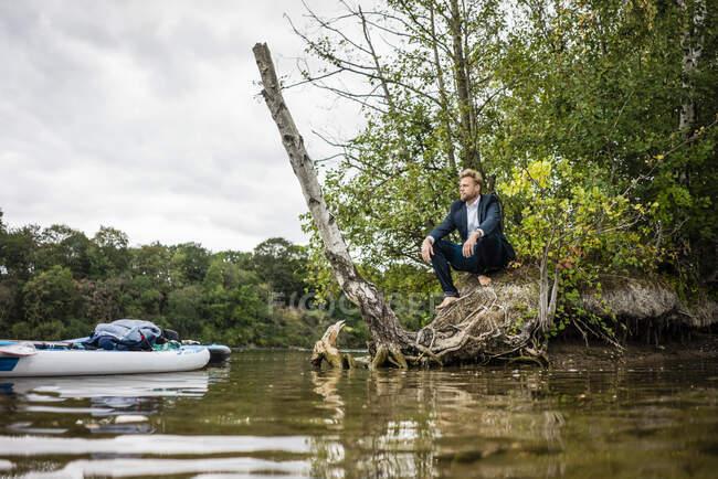 Empresario en la orilla del lago mirando hacia fuera - foto de stock