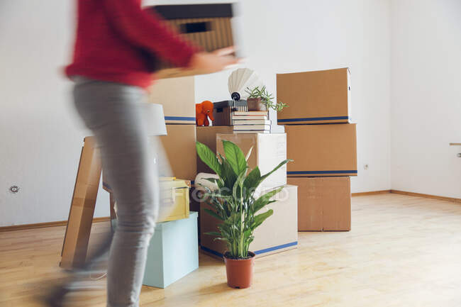 Woman carrying cardboard box in a new home — Stock Photo