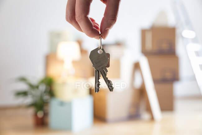 Крупный план женщины, держащей ключи от дома в новом доме — стоковое фото