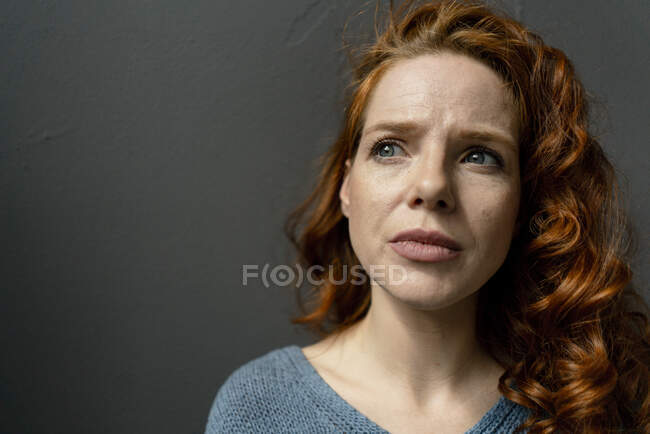 Portrait of pensive redheaded woman against grey background — Stock Photo