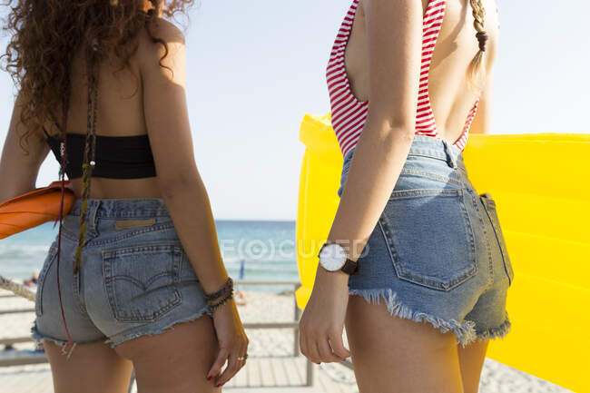Young women with yellow airbed walking to the beach — Stock Photo