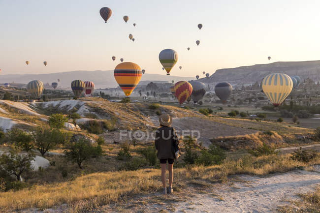 Young woman and hot air ballons, Goreme, Cappadocia, Turkey — Stock Photo