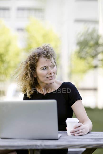 Портрет зрілої комерсантки з ноутбуком і кавою, щоб вийти на вулицю. — стокове фото