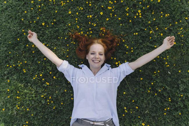 Портрет щасливої рудої жінки, що лежить на квітковій луці. — стокове фото