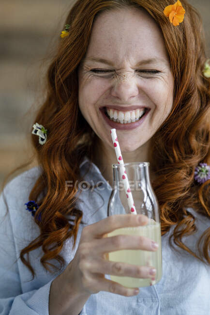 Portrait of laughing redheaded woman with blossoms in hair drinking lemonade — Stock Photo