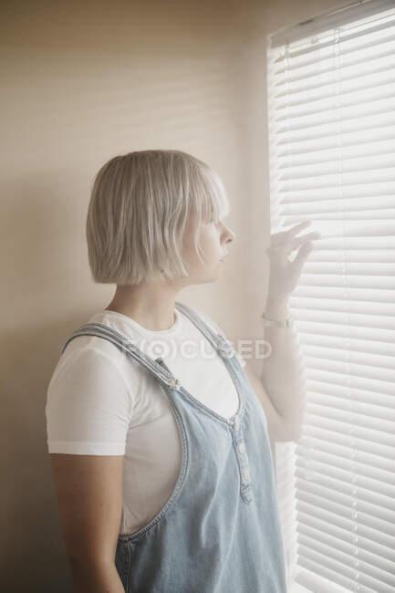 Mujer joven mirando a través de las persianas en la ventana - foto de stock