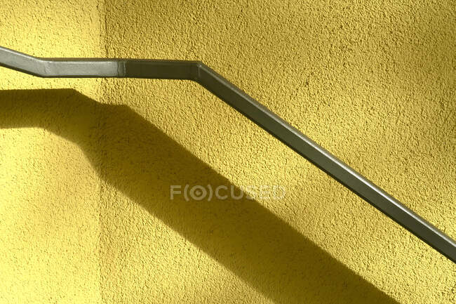 Shadow of handrail on yellow wall — Stock Photo
