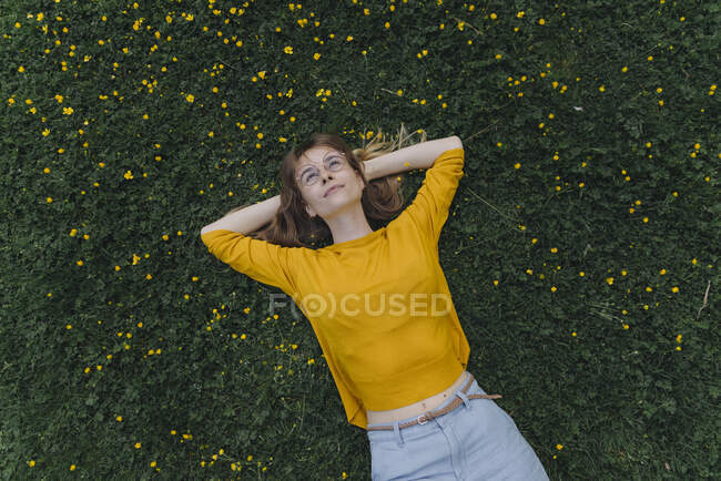 Young woman lying on a flower meadow — Stock Photo