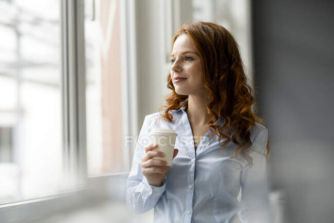 Portrait of redheaded businesswoman with coffee to go looking out of window — Stock Photo
